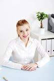 Lächelnde Frau, die hinter dem Schreibtisch sitzt Stockfoto