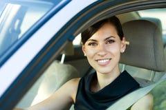 Lächelnde Frau, die ihr Auto antreibt lizenzfreie stockfotografie