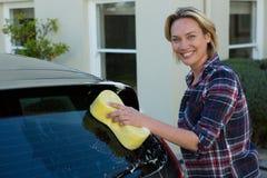 Lächelnde Frau, die ihr Auto mit Schwamm säubert Stockbild