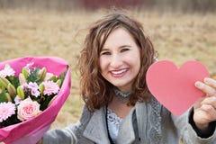 Lächelnde Frau, die ihr Geschenke des Valentinsgrußes zeigt Lizenzfreie Stockbilder