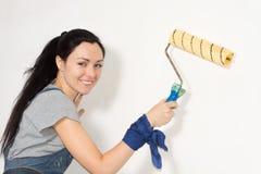 Lächelnde Frau, die ihr Haus malt stockfotos