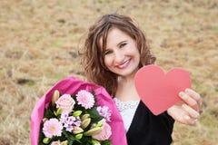 Lächelnde Frau, die ihre Geschenke zeigt Stockbilder