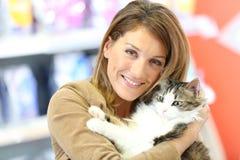 Lächelnde Frau, die ihre Katze hält und streichelt Stockfotografie