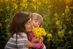 Lächelnde Frau, die ihre nette Tochter, draußen umfasst Stockfotografie