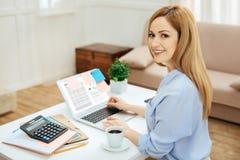 Lächelnde Frau, die an ihrem Laptop vom Haus arbeitet Stockbilder