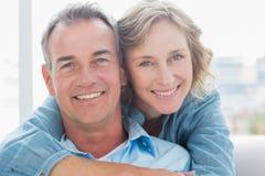 Lächelnde Frau, die ihren Ehemann auf der Couch von hinten umarmt Lizenzfreies Stockfoto