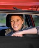 Lächelnde Frau, die im Auto sitzt Stockfotografie