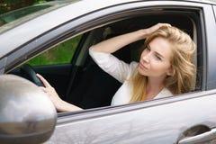 Lächelnde Frau, die im Auto sitzt Lizenzfreie Stockfotografie