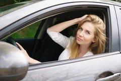 Lächelnde Frau, die im Auto sitzt Lizenzfreies Stockfoto