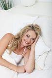 Lächelnde Frau, die im Bett sich entspannt Stockbilder