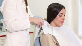 Lächelnde Frau, die im zahnmedizinischen Stuhl während Zahnarzt vorbereitet sie für Kontrolle sitzt stock footage
