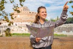 Lächelnde Frau, die Karte hält und nahe Castel StAngelo zeigt Stockfotos