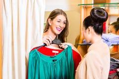 Lächelnde Frau, die Kleidung für das Kaufen vorwählt stockfotos