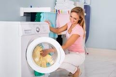 Lächelnde Frau, die Kleidung in Waschmaschine einsetzt stockfotos
