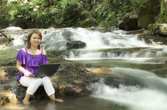 Lächelnde Frau, die an Laptop arbeitet Lizenzfreies Stockbild