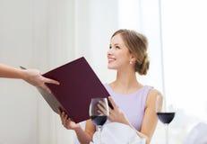 Lächelnde Frau, die Menü vom Kellner empfängt Stockfotografie