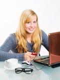 Lächelnde Frau, die mit Computer und Telefon sitzt Stockfotos