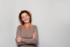 Lächelnde Frau, die mit den Armen gekreuzt steht stockbild