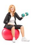 Lächelnde Frau, die mit einem Dummkopf trainiert und auf fitnes sitzt Stockfoto