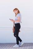 Lächelnde Frau, die mit Handy und Tasche geht Stockfoto