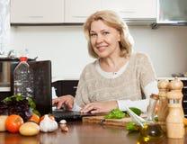 Lächelnde Frau, die mit Notizbuch kocht Lizenzfreies Stockfoto
