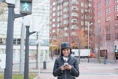 Lächelnde Frau, die Mitteilung am intelligenten Telefon in der Straße, städtisches Lebensstilkonzept schaut Stockfoto