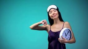 Lächelnde Frau, die am Morgen und Uhr, spätes Wecken, Energie an zu halten ausdehnt lizenzfreie stockfotos