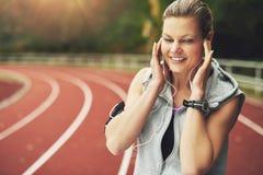 Lächelnde Frau, die Musik auf Bahnfeld hört Lizenzfreie Stockfotos