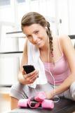 Lächelnde Frau, die Musik an der Turnhalle hört lizenzfreie stockfotos