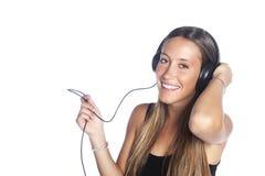 Lächelnde Frau, die Musik mit Kopfhörern hört Stockfoto