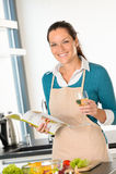 Lächelnde Frau, die nach Hause Küchenrezeptgemüse kocht Stockfoto