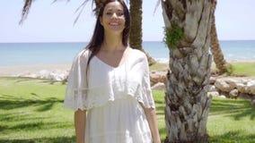 Lächelnde Frau, die nahe Palmen geht stock video footage
