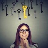 Lächelnde Frau, die oben goldenem Schlüssel der Weinlese zum Erfolg unter vielen hängenden anderen betrachtet lizenzfreie stockbilder