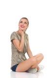Lächelnde Frau, die oben sitzt und schaut Stockfotos