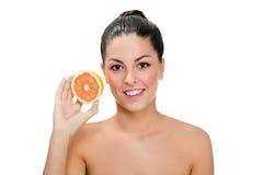 Lächelnde Frau, die orange Scheibe hält Lizenzfreie Stockfotografie