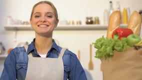 Lächelnde Frau, die Papiertüte mit frischem Brot, Obst und Gemüse betrachtet stock footage