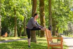 Lächelnde Frau, die in Park am sonnigen Tag ausdehnt lizenzfreie stockbilder