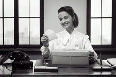 Lächelnde Frau, die per Post eine Geschenkbox empfängt Lizenzfreies Stockfoto