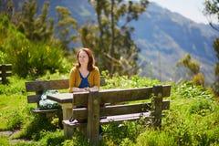 Lächelnde Frau, die am Picknicktisch sitzt Stockbild