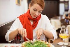 Lächelnde Frau, die Pizza mit Arugula im italienischen Restaurant isst lizenzfreies stockbild