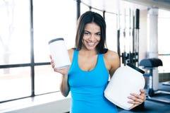 Lächelnde Frau, die Plastikbehälter mit Sportnahrung hält Stockfotografie