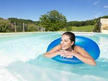 Lächelnde Frau, die in Pool schwimmt Lizenzfreie Stockbilder
