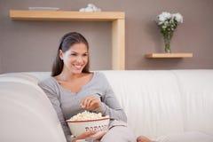 Lächelnde Frau, die Popcorn beim Überwachen eines Films isst stockfoto
