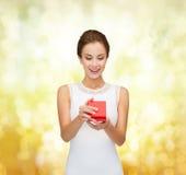 Lächelnde Frau, die rote Geschenkbox hält Stockfotografie