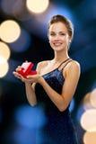 Lächelnde Frau, die rote Geschenkbox hält Stockfoto