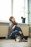 Lächelnde Frau, die sich zu Hause entspannt Stockbild