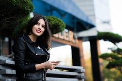 Lächelnde Frau, die sms auf der Straße sendet Lizenzfreie Stockbilder