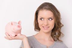 Lächelnde Frau, die Sparschwein betrachtet Stockfotos