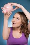 Lächelnde Frau, die Sparschwein betrachtet Lizenzfreies Stockbild