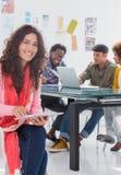 Lächelnde Frau, die Tablette mit dem kreativen Team hinten arbeitet verwendet Stockbild
